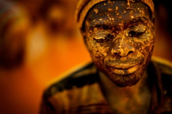 A miner has his face spattered with mud from working in a small scale gold mine