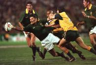 South African's Joost Van der Westhuizen (R) passes the ball after a tackle by Australian back Stephen Larkham ( R) and flyhalf George Gregan (C) during the final of the tri-nations cup August 22. South Africa beat the visiting Australians 29-15.  JN/KM - RTRX0CH